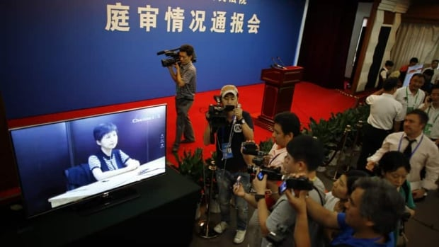 Journalists watch the testimony of Gu Kailai, wife of ousted Chinese politician Bo Xilai. Bo has questioned his wife's credibility and mental health.
