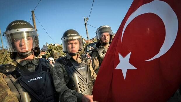 Paramilitary police officers block a man holding a national flag outside the Silivri jail in Turkey, where a court Monday sentenced a retired military chief and some MPs to prison terms for trying to overthrow the government.