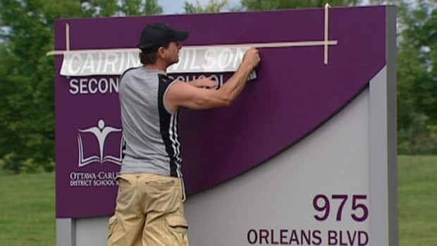 "A man fixed the new sign for Cairine Wilson Secondary School in Orleans on Saturday. The sign originally read, ""Carnie Wilson Secondary School."""