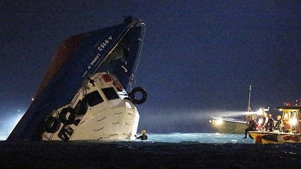 Rescuers check on a half submerged boat after it collided with another vessel Monday night near Lamma Island, off the southwestern coast of Hong Kong.