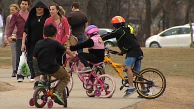 Young cyclists - some wearing helmets, some not - ride on the trails at Winnipeg's Assiniboine Park in March.