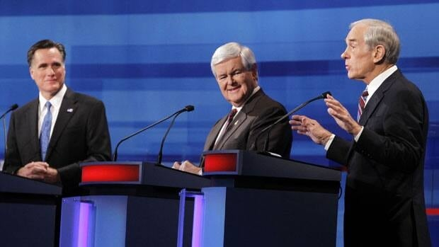 Former Massachusetts Governor Mitt Romney and former House Speaker Newt Gingrich listen to U.S. Rep. Ron Paul speaks in a Republican presidential candidates debate South Carolina.