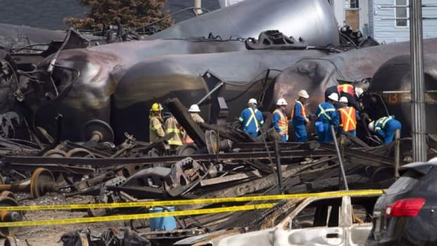 Workers are seen in this July 16 photo at the site of the train derailment and fire in Lac-Megantic, Que. The bankrupty railway whose train derailed could be sold by the end of the year, a trustee says.