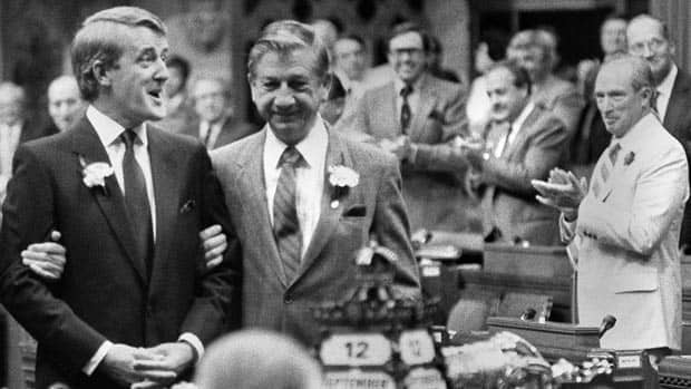 Conservative leader Brian Mulroney is given a standing ovation by Prime Minister Pierre Trudeau (R) while being escorted into the House of Commons Sept. 12, 1983.