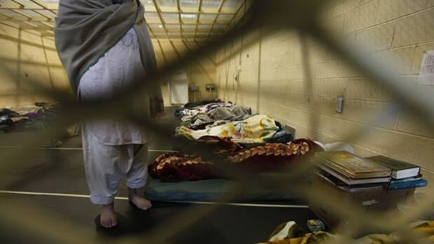 In this March 23, 2011 photograph, Afghan detainees are seen through mesh wire fence inside the Parwan detention facility near Bagram Air Field in Afghanistan.