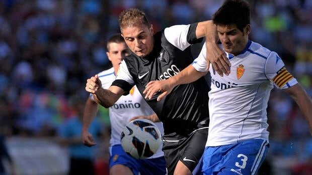 Joaquin Sanchez of Malaga duels for the ball with Javier Paredes of Resal Zaragoza during their match on Saturday.