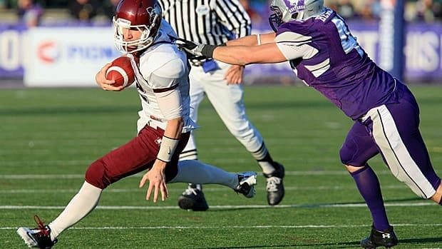 McMaster Marauders quarterback Kyle Quinlan scrambles away from Western Mustangs Rob Hennessey during second-half Yates Cup action in London.