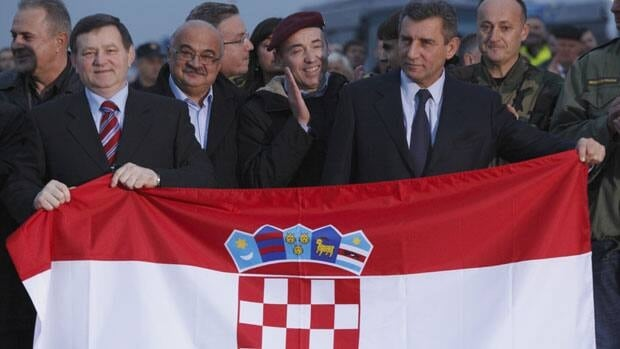 Police commander Mladen Markac, left, and General Ante Gotovina, right, hold the Croatian flag after arriving Friday in Croatia.