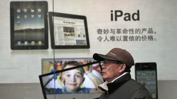 A man stands near Apple's iPad advertisement in Shanghai, China. A Chinese court said Monday that Apple Inc. has agreed to pay $60 million to a Chinese technology firm to settle a dispute over the global rights to the iPad name.