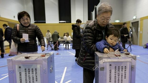 A boy places his grandmother's vote into a ballot box at a polling station in Tokyo on Sunday. Voters cast their ballots in parliamentary elections which are likely to hand power back to a conservative party that ruled Japan for most of the post-war era.