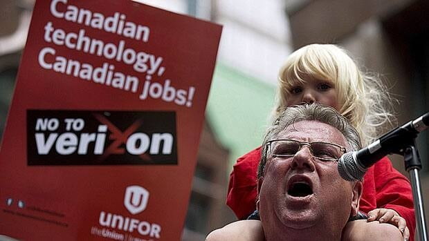 Canadian Auto Workers' outgoing president Ken Lewenza holds a union member's daughter as he speaks against Verizon Wireless coming to Canada during a rally in Toronto last Friday. The American wireless giant announced this week it will not come to Canada.