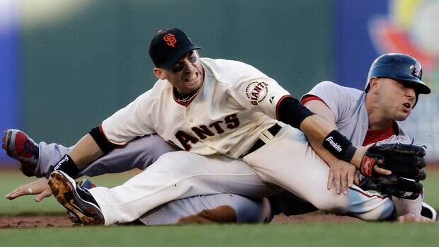 San Francisco Giants second baseman Marco Scutaro grimaces as his leg is caught under a sliding St. Louis Cardinals' Matt Holliday on a double play attempt during the first inning of Game 2.