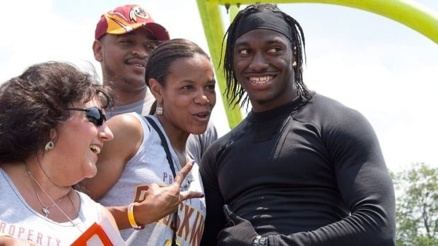 Washington Redskins' quarterback Robert Griffin III poses for a photo with fans during an NFL football minicamp at Redskins Park last month in Ashburn, Va.