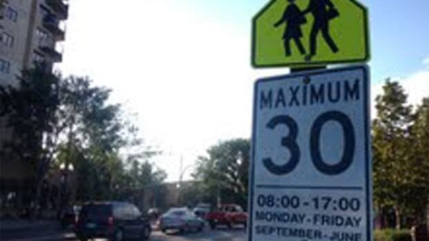 A school zone sign at Broadway & 12th Street East in Saskatoon signaling drivers to slow down as they approach Ecole Victoria School.