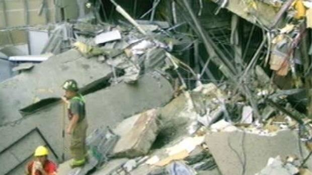 Rescue workers try to reach two people trapped inside the Algo Centre Mall in June, 2012.