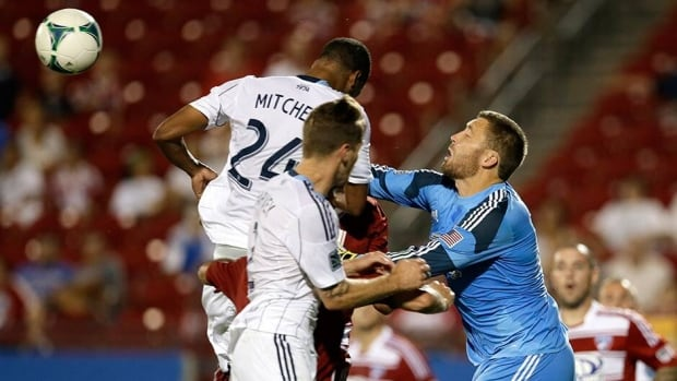 FC Dallas goalkeeper Chris Seitz (18) clears a shot under pressure from Vancouver Whitecaps Carlyle Mitchell (24) and Jordan Harvey, front, in the second half Saturday.