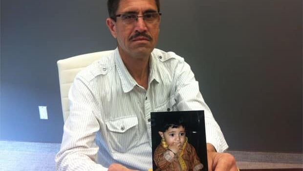 Ashfaq Afridi holding a picture of, Ajjab, the son he and his wife want to adopt from Pakistan.