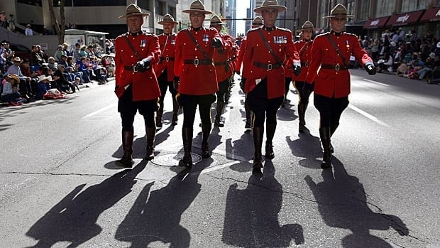 Members of the RCMP march during the Calgary Stampede parade on July 5. A proposed new code of conduct has been drafted to address harassment in the ranks and use of force among other things.