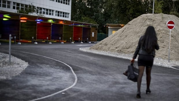 A sex worker walks toward the so-called sex boxes opened last month in Zurich as part of a new drive-in prostitution zone, designed to make sex work safer and remove it from city streets. Clients can pull their cars into the boxes to conclude transactions in semi-privacy.
