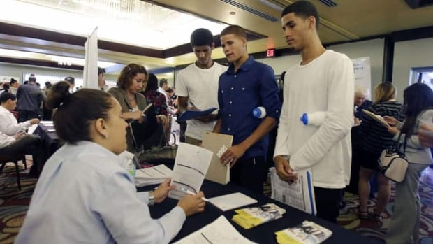 Job seekers talk to a FirstService representative at a job fair in Miami Lakes, Fla. on Aug. 14. The Labor Department reports on the number of Americans who applied for unemployment benefits is falling, but youth unemployment is above 22 per cent.