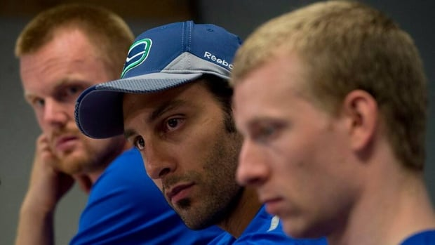 Vancouver Canucks Daniel Sedin, left, goaltender Roberto Luongo, centre, and Jannik Hansen attend a media availability at Rogers Arena in Vancouver on Wednesday.