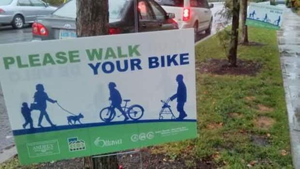 Some Centretown residents have put up signs asking cyclists to walk their bikes along sidewalks.
