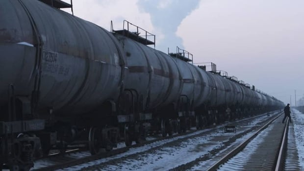 A worker walks beside an oil tank train in China. An analyst says oil by rail bottlenecks in North America will soon be cleared, and the Keystone XL pipeline won't be needed.