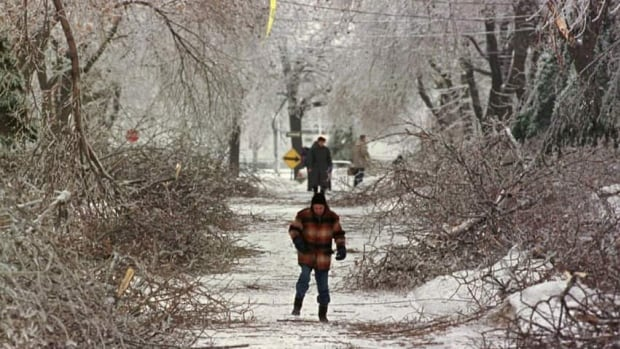 Pedestrians in Montreal make their way past broken branches during the Quebec ice storm on Wednesday, Jan.7, 1998.