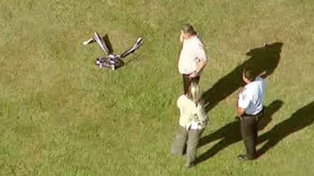 Investigators stand near a remote controlled toy helicopter that apparently struck and killed a 19-year-old man on Thursday in a Brooklyn park.