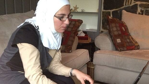 Dima Alsayed reads news from Syria on her laptop in Winnipeg on Monday.