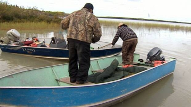 Searchers examine the boat belonging to Frank Black that was found Monday on Russell Lake. Black, 57, of Behchoko, N.W.T., was last seen Aug. 29.