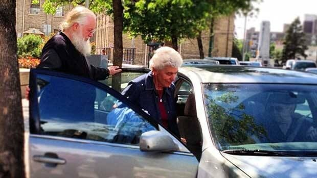 Archbishop Kenneth (Seraphim) Storheim, left, and a supporter leave the Winnipeg courthouse in June.