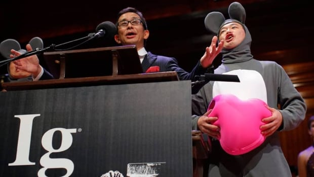 Masanori Niimi of Japan and his colleague Xiangyuan Jin, dressed as a mouse, received the 2013 Ig Nobel Medicine Prize for 'assessing the effect of listening to opera, on heart transplant patients who are mice.'