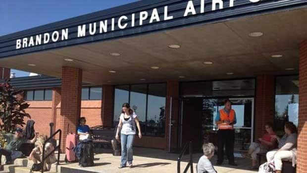 WestJet passengers wait outside the Brandon Municipal Airport on Tuesday, as their flight was delayed after a small private plane crashed at the airfield.