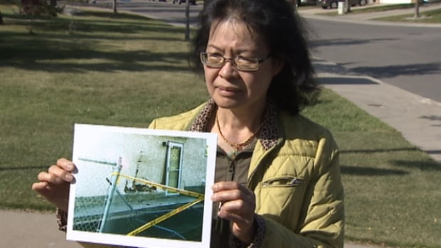 Tina Lowe holds a photograph showing the damage to the side of her garage. An SUV crashed into the side of the building early Sunday morning.