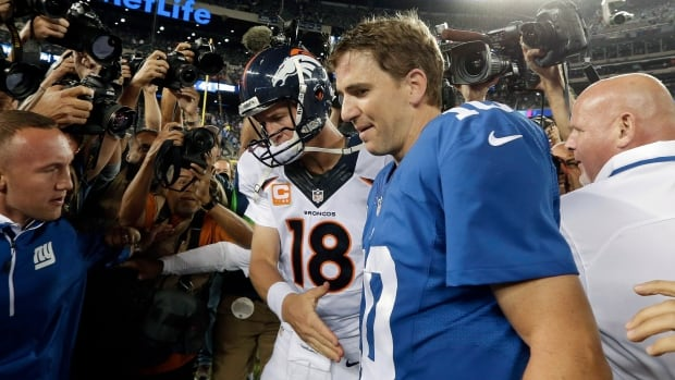 Denver Broncos quarterback Peyton Manning, left, shakes hands with his brother New York Giants' quarterback Eli Manning, right, after an NFL football game on Sunday in East Rutherford, N.J. The Broncos won the game 41-23.