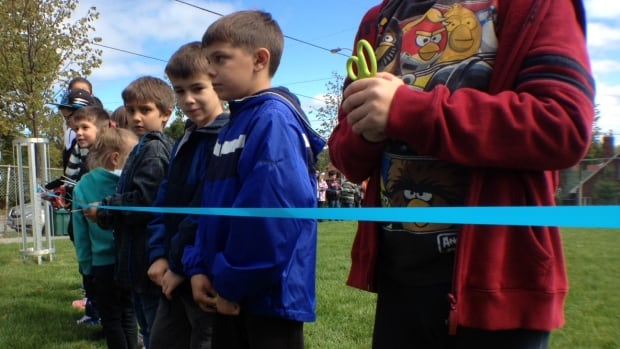 Students at Alexander Public School get ready to cut the ribbon on their new green play area.