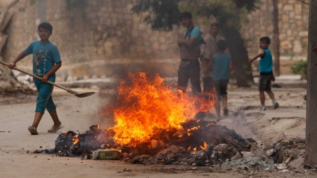 Residents gather and burn trash in Aleppo, Syria, on Wednesday. The conventional war in Syria continued today as a bomb exploded on a bus, killing 19.