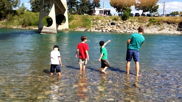 Rosa Marchitelli's husband Rob Brown and their three sons throw rocks in the Bow River.