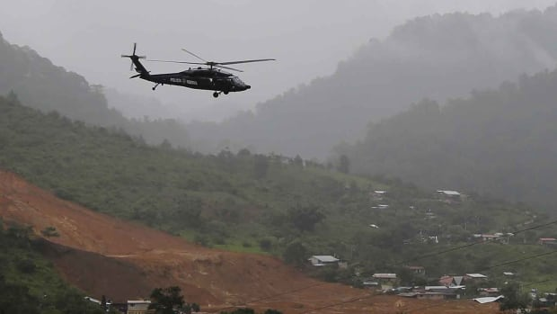 A helicopter of the Mexican federal police flies over a mudslide in the remote mountain village of La Pintada, Guerrero. A helicopter with three crew members on board went missing on Thursday while returning from La Pintada.