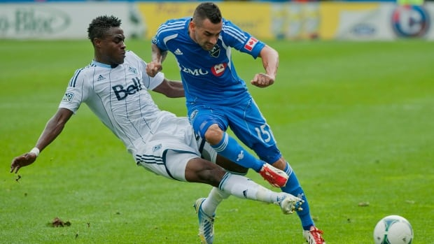 Montreal Impact's Andres Romero, right, and Whitecaps' Gershon Koffie battle for the ball during first half MLS soccer action in Montreal on Saturday. Vancouver went on to win the game 3-0, despite plenty of offensive pressure by the Impact late in the game.