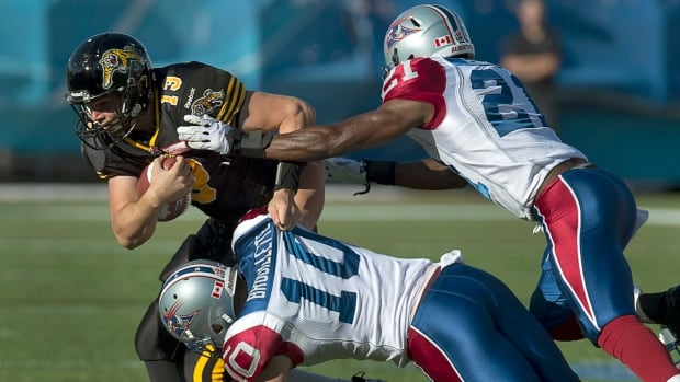 Tiger-Cats Dan LeFevour, left, is tackeld by Montreal Alouettes Marc Brouillette and Mike Edem, right, in first half CFL action in Moncton, N.B. on Saturday. LeFevour's one-yard touchdown in the fourth quarter helped Hamilton take home the victory.