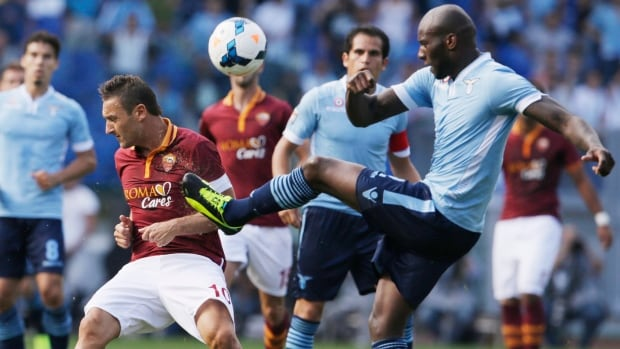 AS Roma forward Francesco Totti, left, and Lazio defender Andre' Dias fight for the ball during their match in Rome's Olympic stadium on Sunday.