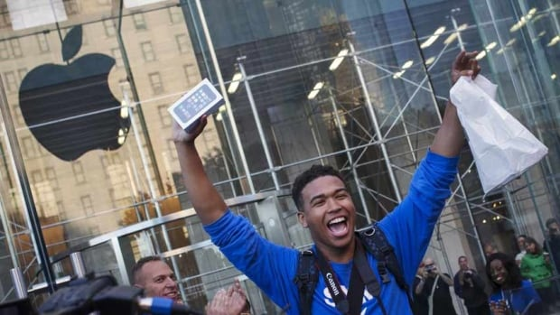 One of the first customers to purchase the Apple iPhone 5S celebrates after exiting the Apple retail store on Fifth Avenue in Manhattan on Friday.