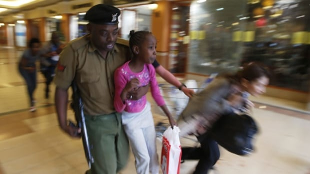 A soldier carries a child to safety shortly after the attack on the Westgate shopping centre in Nairobi. One survivor told CBC News of the injured leaving in private cars in the immediate aftermath.