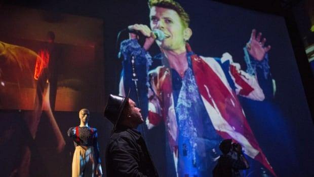 A visitor watches an audio-visual display at the David Bowie Is exhibition.