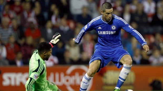 Chelsea's  Fernando Torres, right, vies for the ball with Swindon's goalkeeper Wes Foderingham during the English League Cup soccer match between Chelsea and Swindon Town at the County Ground in Swindon, England Tuesday, Sept. 24, 2013. (AP Photo/Kirsty Wigglesworth)