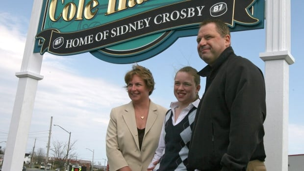 Trina, Taylor and Troy Crosby (left to right), the family of NHL star Sidney Crosby, pose for photos in front of a sign constructed in 2008 marking Cole Harbour, N.S., near Halifax, as the home of Sidney Crosby in 2008.