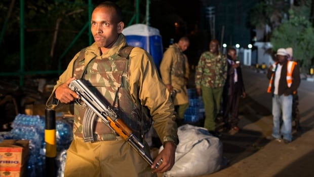 A Kenyan police officer patrols a security perimeter at the Westgate Shopping Centre in Nairobi on Tuesday. Al-Shabaab militants attacked the mall over the weekend and launched a second attack on a Kenyan border posting.