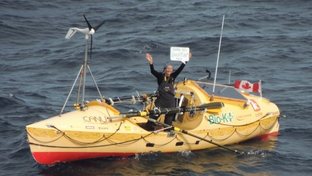 Mylène Paquette, a Canadian rower attempting to make history by becoming the first North American woman to successfully row solo across the North Atlantic, holds up a sign thanking the people on the ocean liner Queen Mary 2.